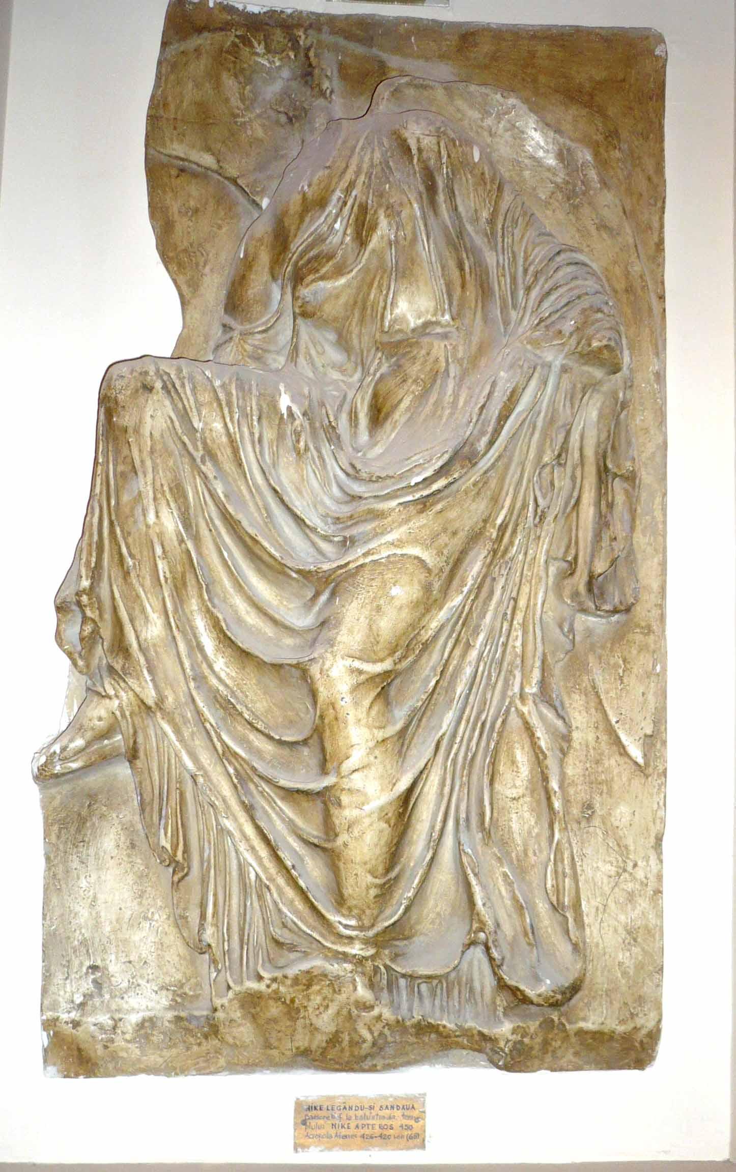 Nike (Victoria) legându-şi sandaua – Basorelief pe balustrada Templului Nike Apteros, Acropola Atenei (Copie în gips realizată în Muzeul Luvru)